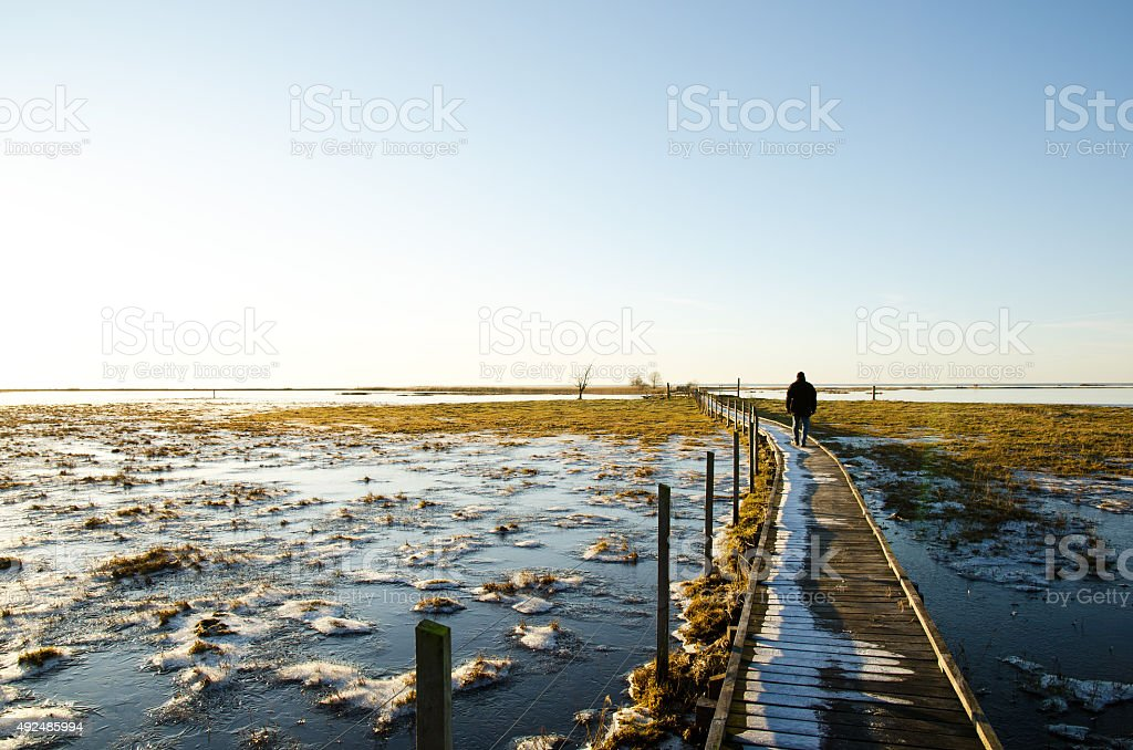 Man walking on a footbridge stock photo