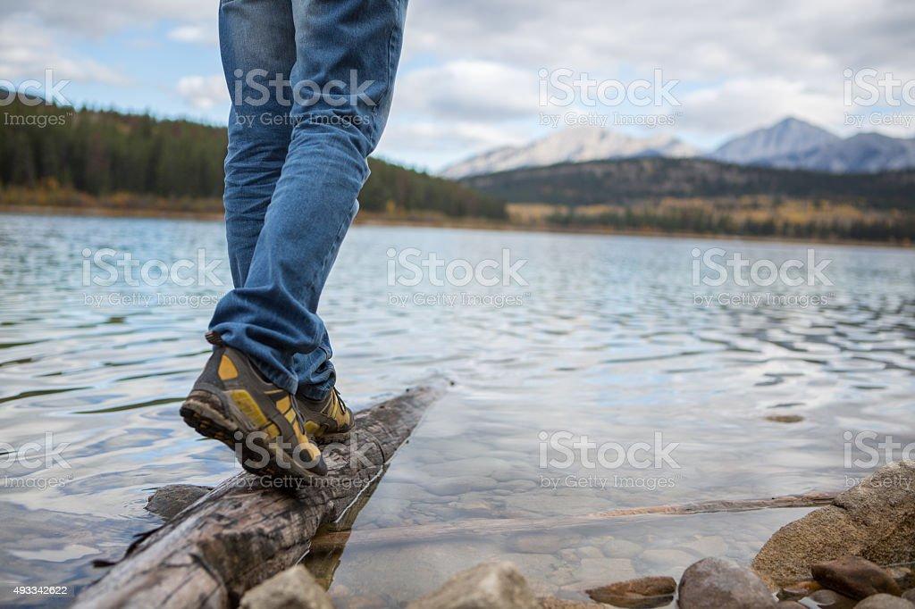 Man walking on a tree log on the lake stock photo