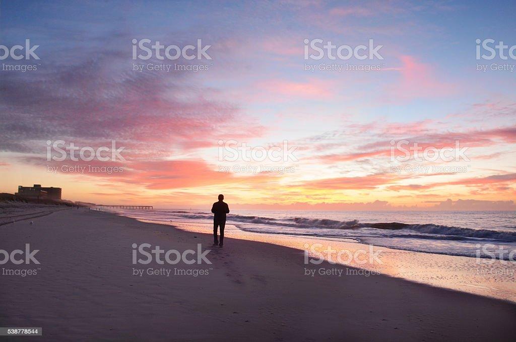 Man walking on beach at beautiful sunrise. stock photo