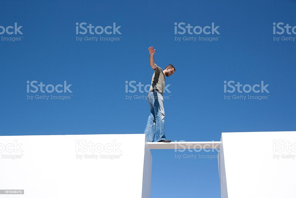 Man walking on board between two walls outdoors stock photo
