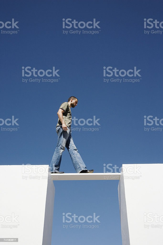 Man walking on board between two walls outdoors royalty-free stock photo