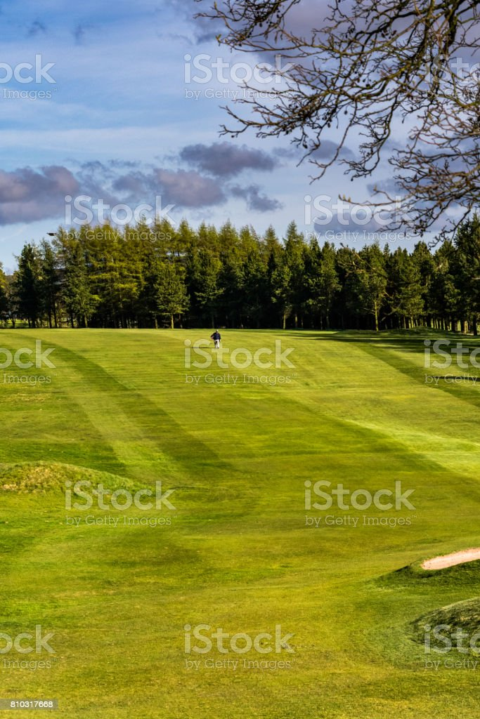 Man Walking on Green Golf Course stock photo