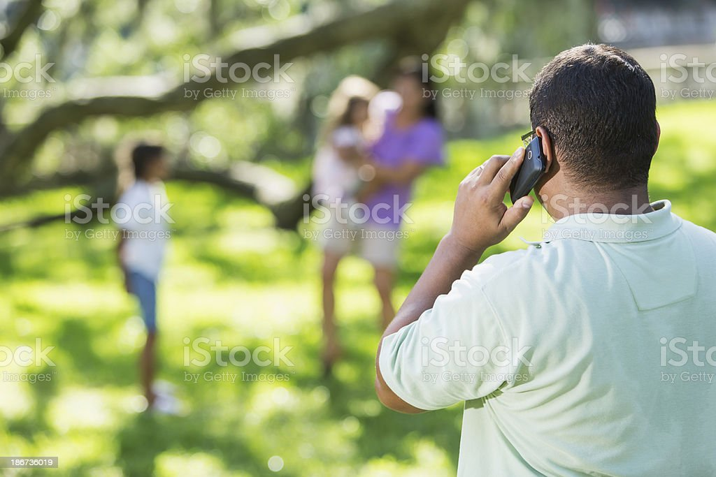 Man walking on phone, family in background stock photo