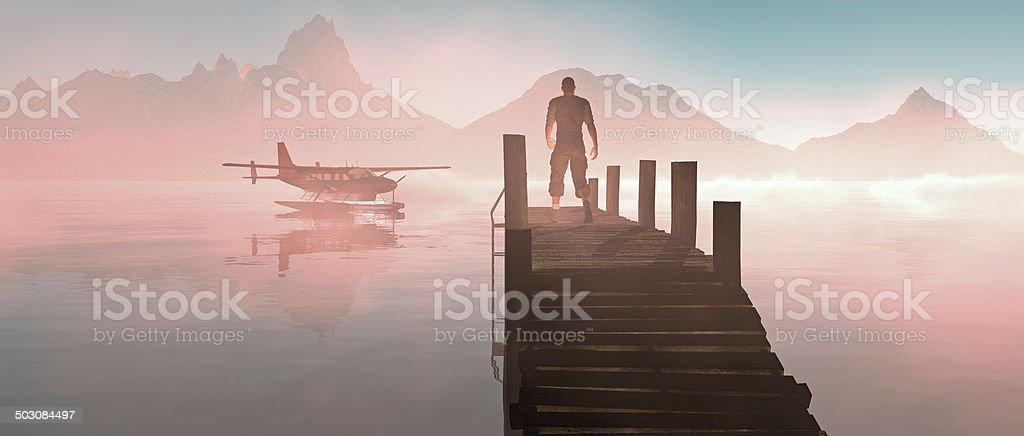 Man walking on pier at lake with floating airplane. stock photo