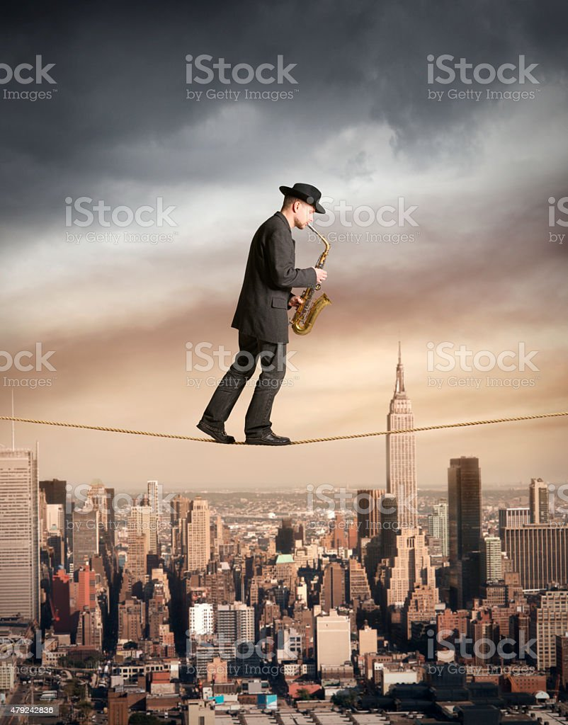 Man walking on rope and playing saxophone in NYC stock photo