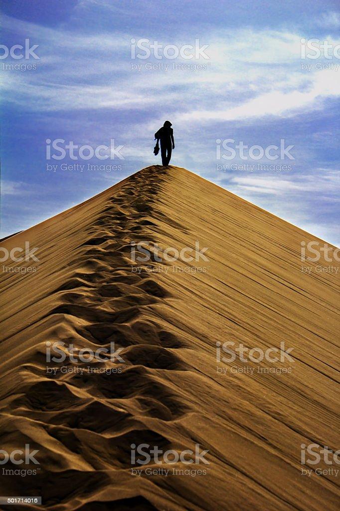 Man walking on sand dunes in the desert stock photo