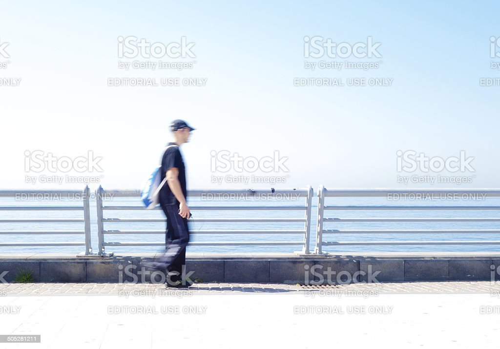 Man walking on sea promenade royalty-free stock photo
