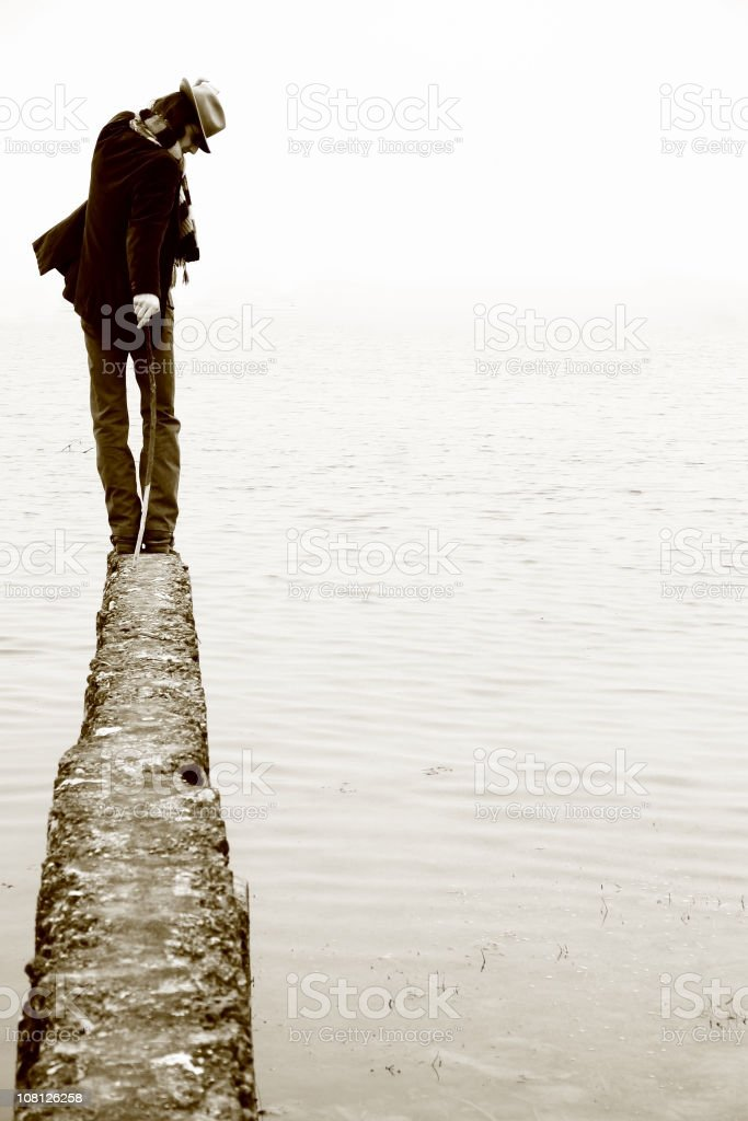 Man Walking on Skinny Ledge Looking Out Over Water royalty-free stock photo