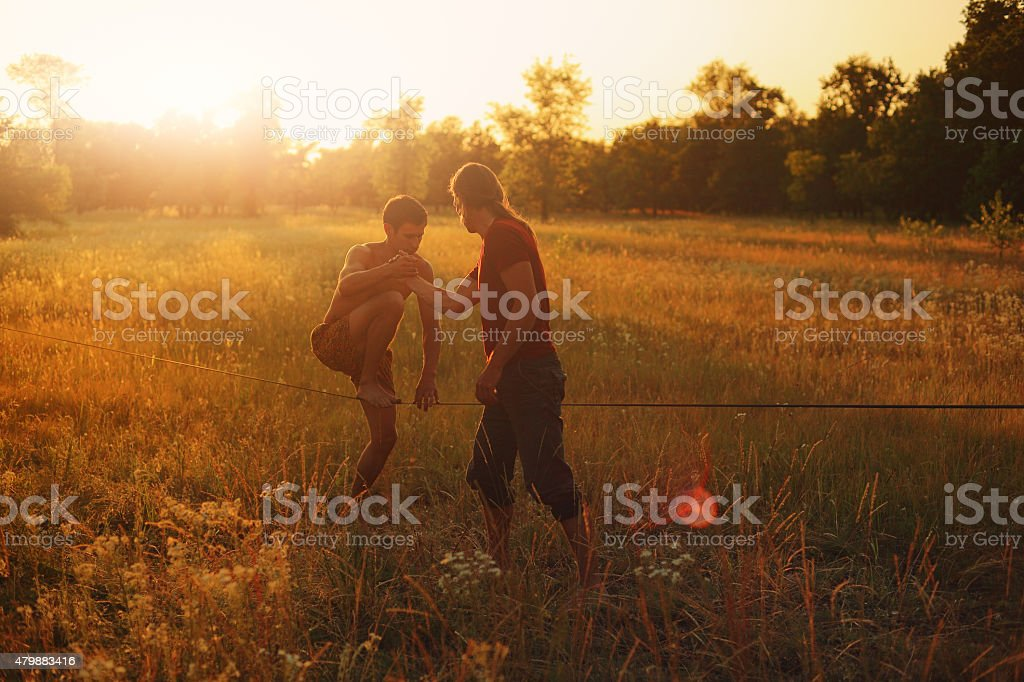 Man walking on slackline in the meadow at sunset. stock photo
