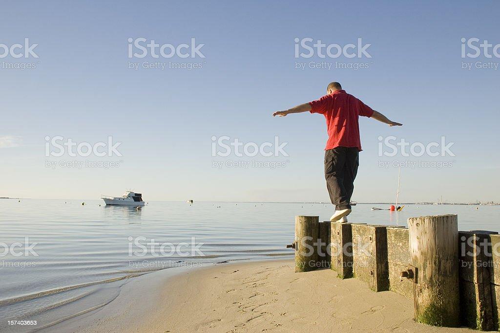 Man walking on stones near the sea royalty-free stock photo