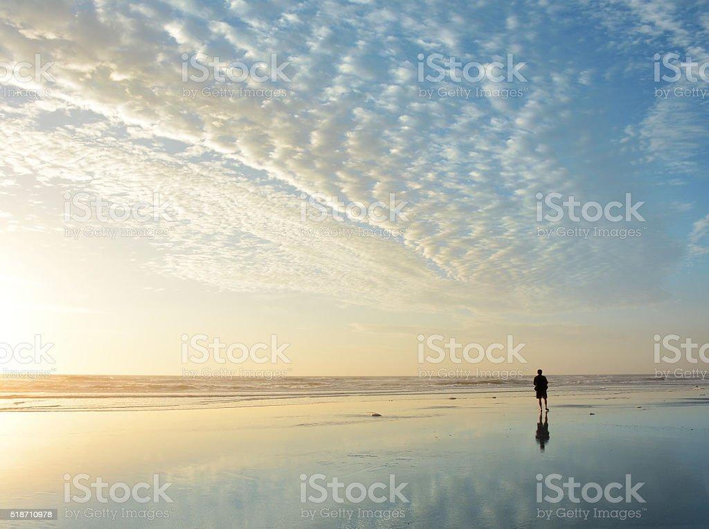 Man walking on the beach at sunrise. stock photo