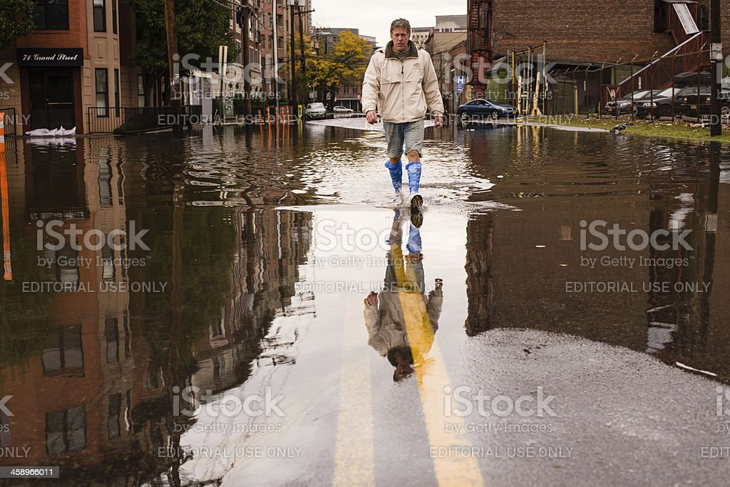 Man walking on the flooded street after Hurricane Sandy landfall stock photo
