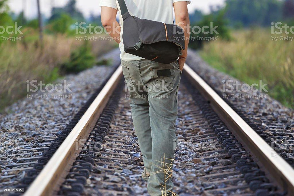 man walking on the railway tracks stock photo