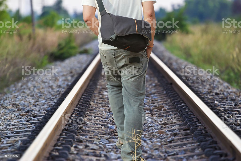 man walking on the railway tracks stock photo