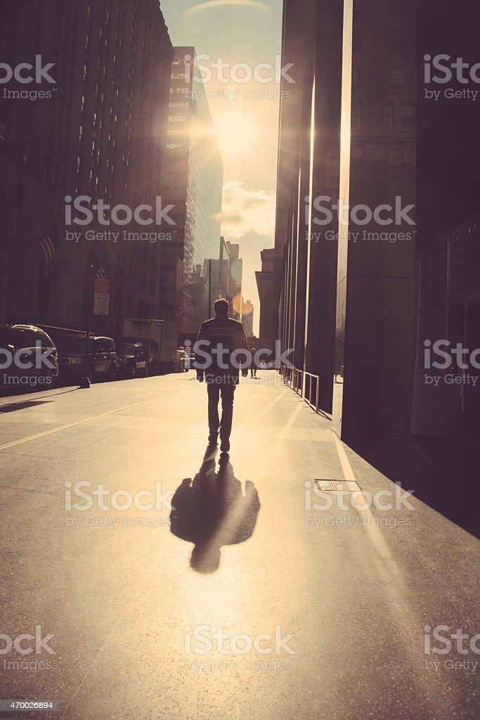 Man walking on the street of New York at sunrise stock photo
