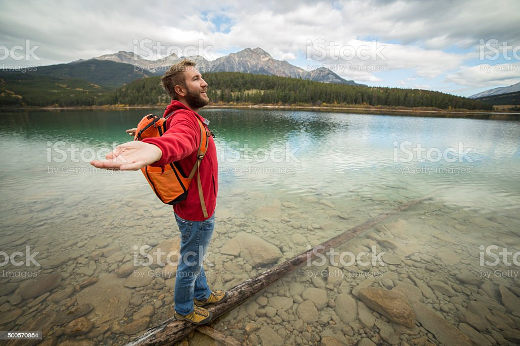 Man walking on tree log on lake arms outstretched stock photo