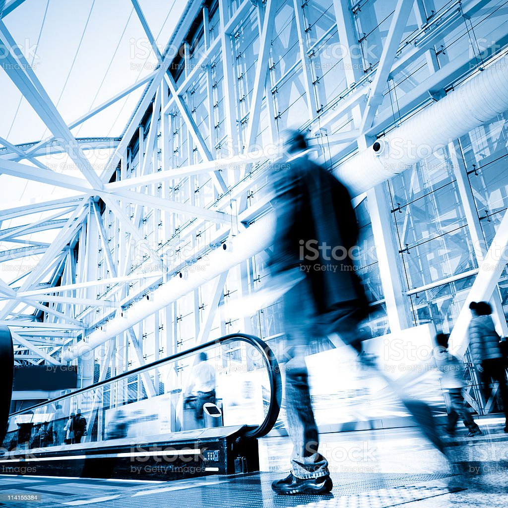 Man walking onto escalator with speed blur royalty-free stock photo