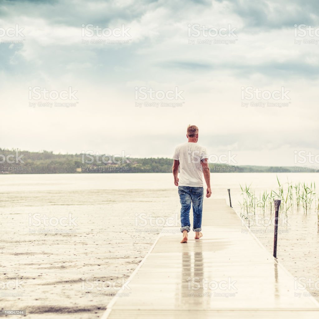 Man walking out on a pier royalty-free stock photo