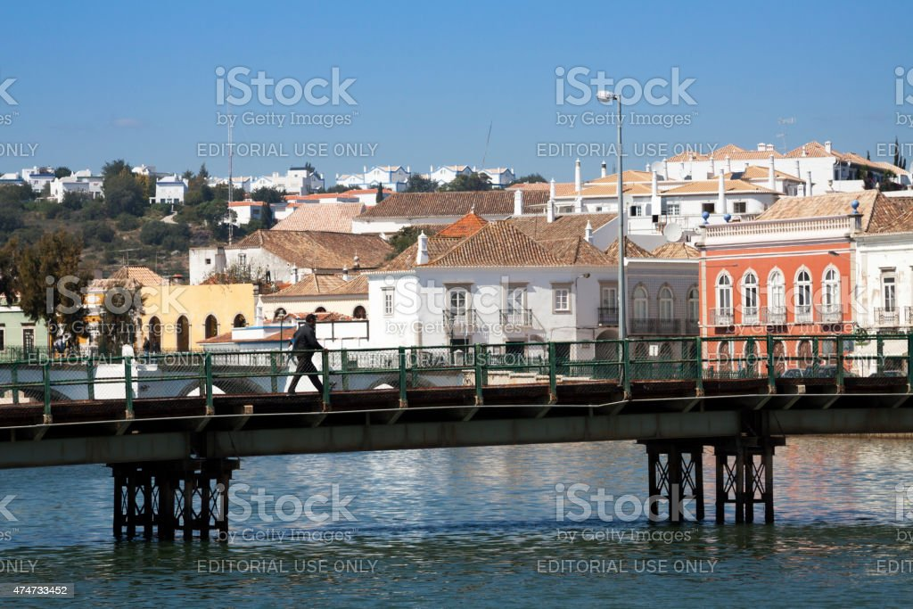Man walking over the temporary bridge in Tavira stock photo