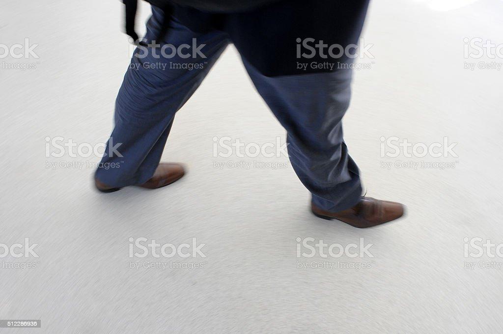man walking quickly stock photo
