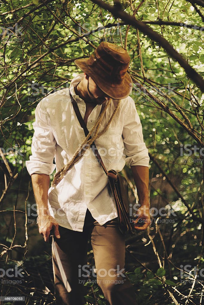 Man walking through forest with machete stock photo