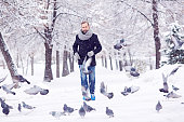 Man walking through snowy park, pigeons flying around him