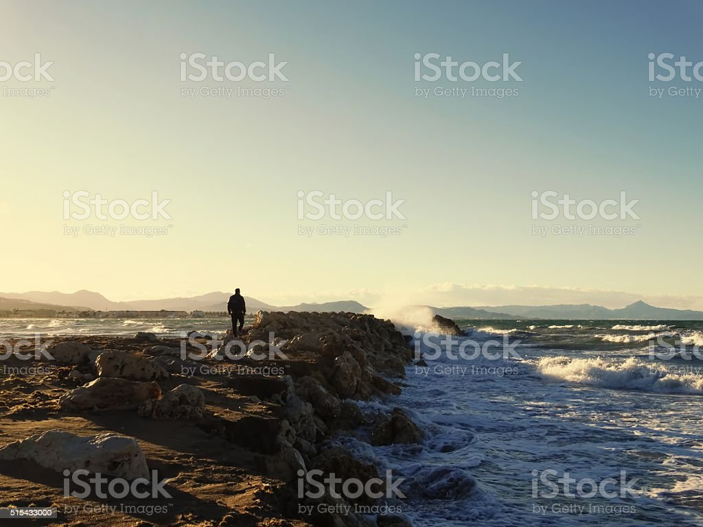 Man walking to the sea on the breakwater, wave splash stock photo