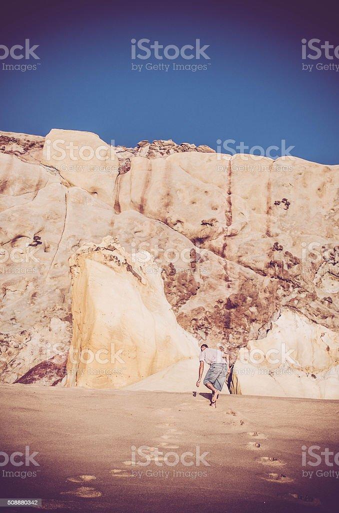 Man walking up the dunes stock photo