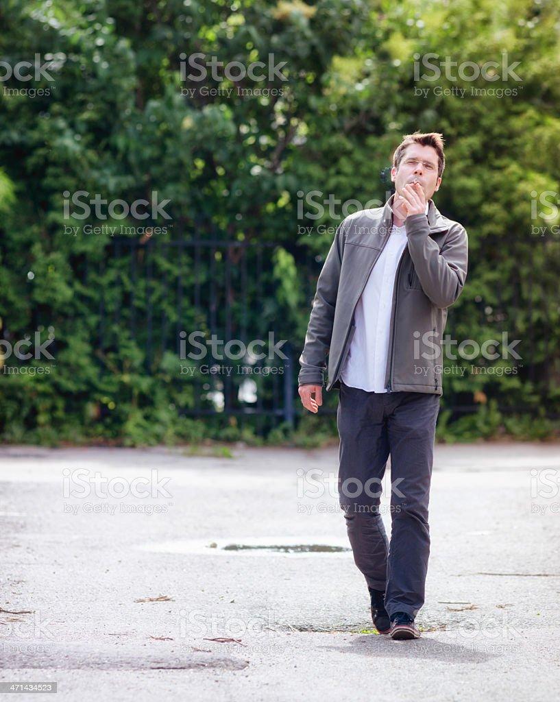 Man walking while smoking in alley full length royalty-free stock photo
