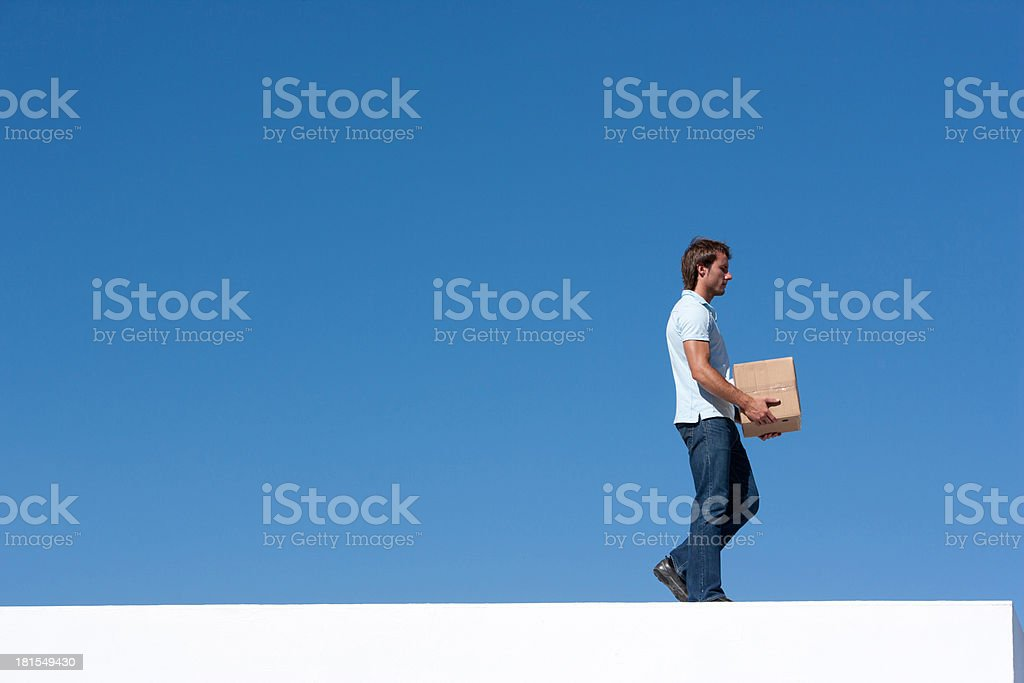 Man walking with cardboard box outdoors with blue sky stock photo