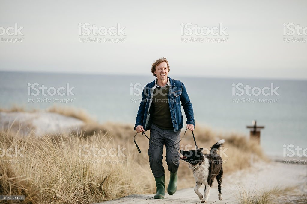 Man walking with his dog stock photo