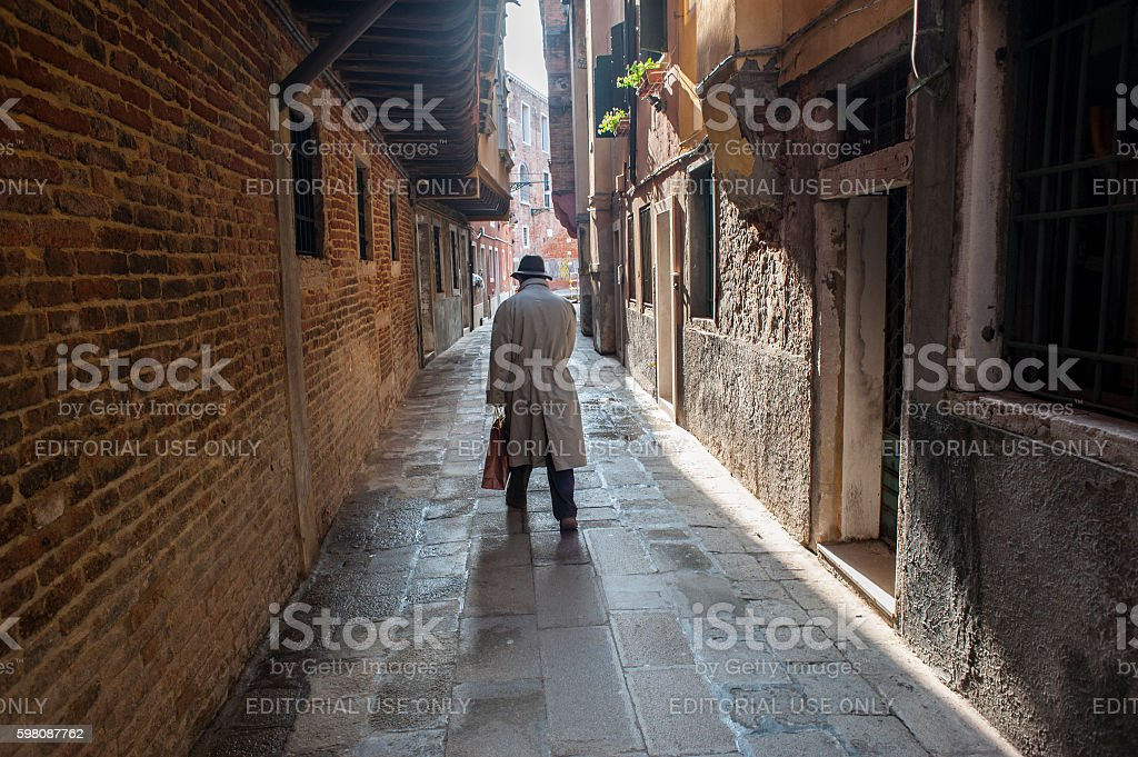 Man walks away in an alley in Venice stock photo