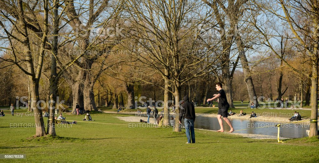 A man walks on a slackline while other people relax stock photo