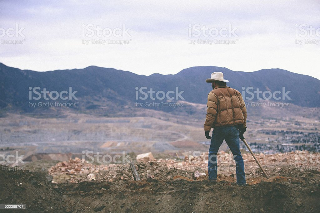 Man walks on mound of work site surrounded by moutains royalty-free stock photo