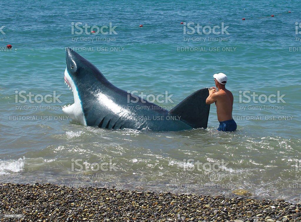 Man walks with a hoax sharks the beach in Sochi stock photo