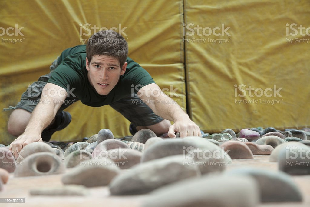 Man wall-climbing in indoor facility with yellow mats below stock photo