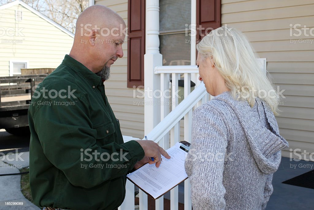 Man wanting woman to sign paper in front of house stock photo