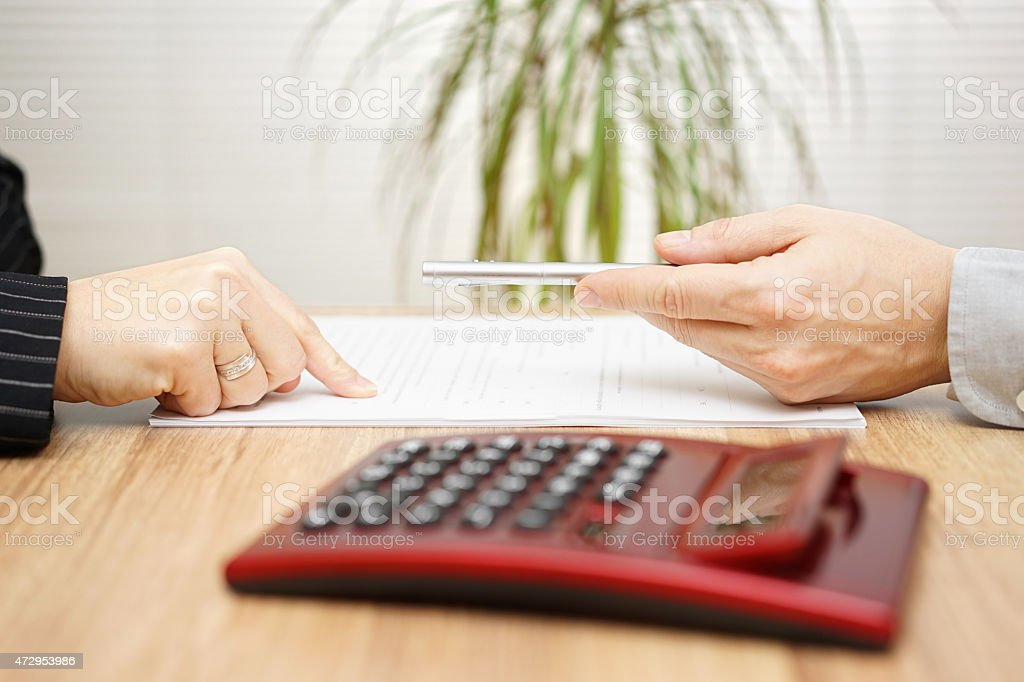Man wants a woman to sign a contract, woman wants correction on contract stock photo
