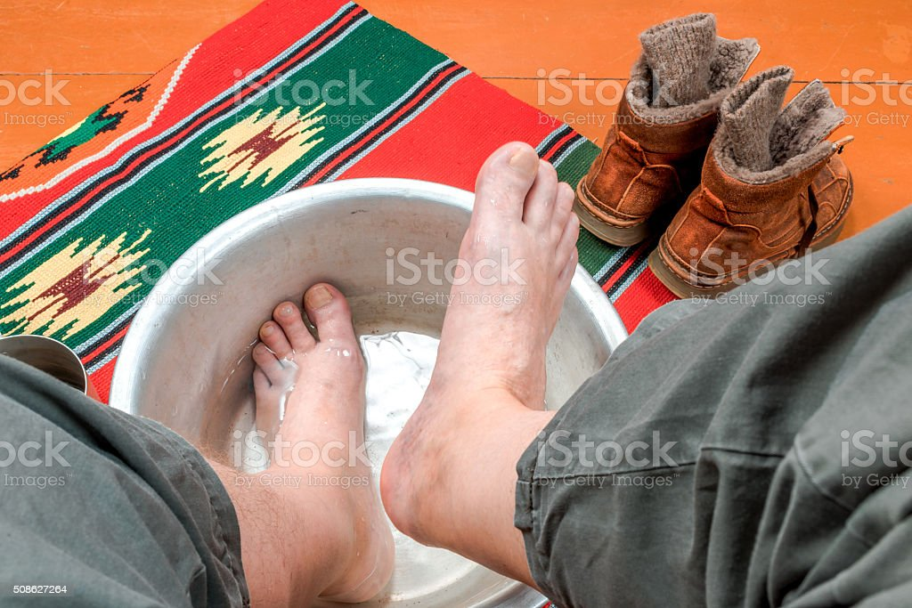 Man warms his feet in a basin of water stock photo