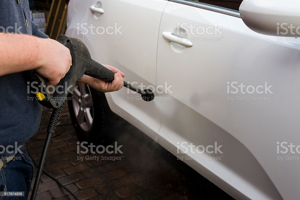 Man washing a white car door with a pressure washer. stock photo