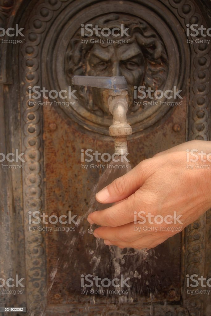 Man Washing Hands at Antique Iron Water Fountain stock photo