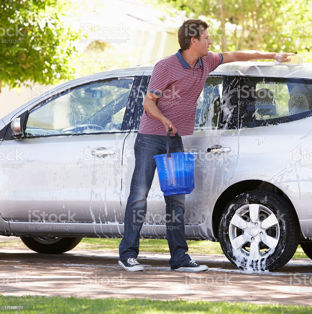 Man washing his car in driveway stock photo