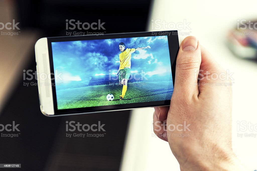 Man watches a football match on phone royalty-free stock photo