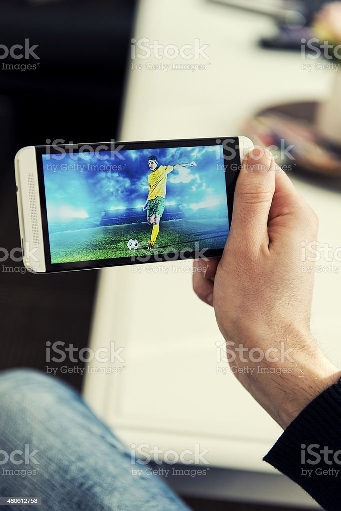 Man watches a soccer match on phone royalty-free stock photo