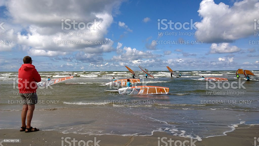Man watches the competition on the seashore stock photo