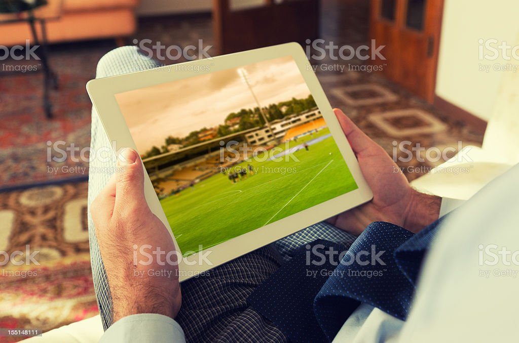 Man watching a soccer tv game on digital tablet royalty-free stock photo