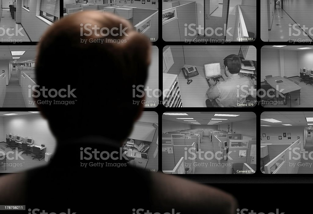 Man watching an employee work via a closed-circuit video monitor stock photo