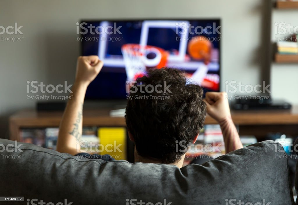 Man watching basketball on tv stock photo