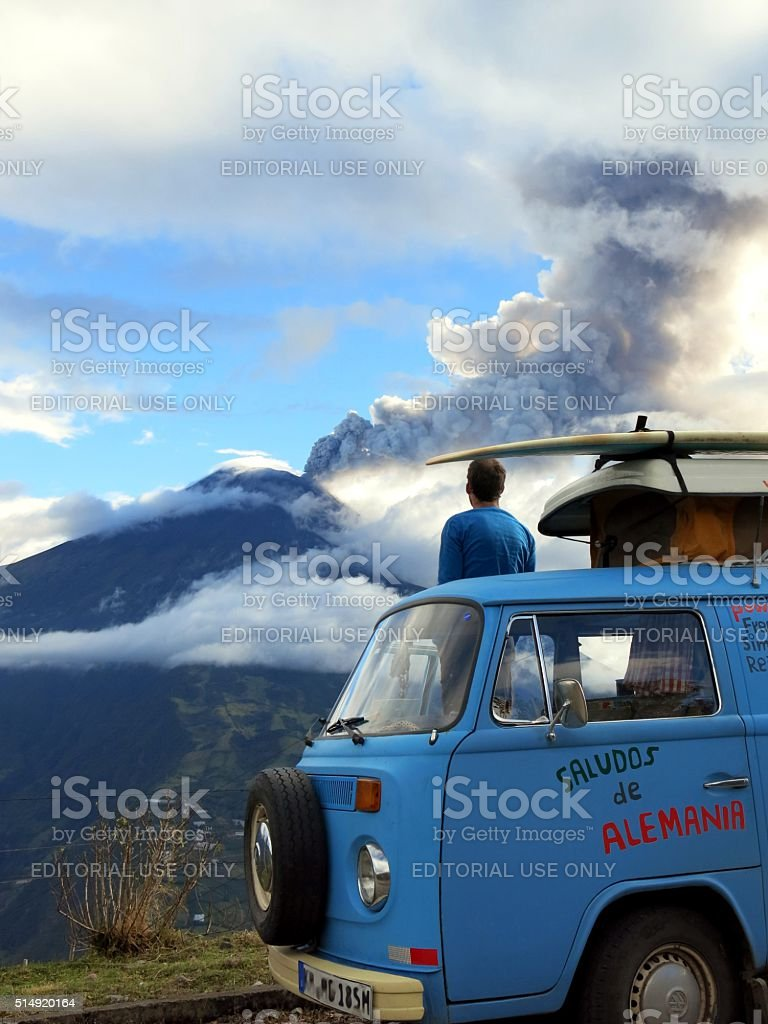 Man watching erruption of volcan Tungurahua from Vw Bus stock photo