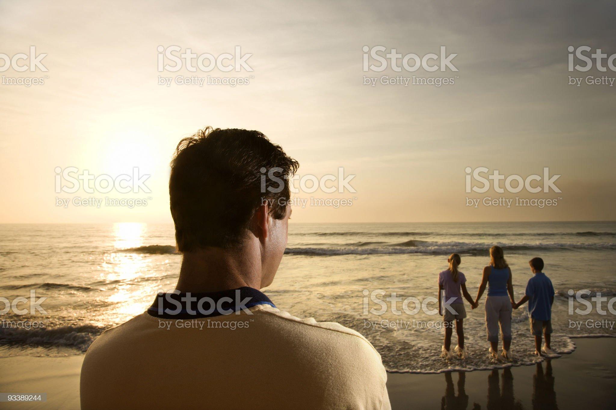 Man watching family at beach royalty-free stock photo